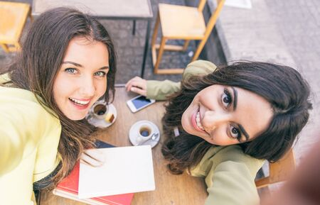 self dependent: Two young women taking selfie with smart phone in the city center. Happiness concept about people and technology