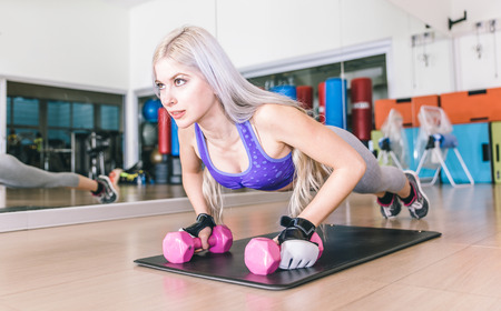 weight training: Beautiful girl making push ups on dumbbells. Concept about fitness and sport