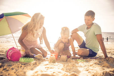 Happy family playing on the beach and build some sand castle photo