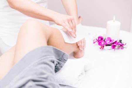 depilacion con cera: Mujer que hace la depilación en sus piernas en un salón de belleza Foto de archivo