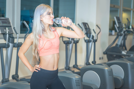 Beautiful girl drinking water in the gym after long training. Sport and healthy lifestyle Stock Photo