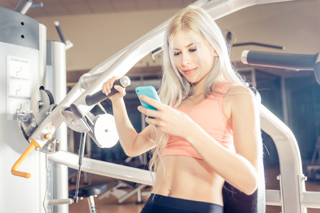 female beauty: woman making training in the gym and checking her schedule on the phone. Lifestyle concept about sport, fitness and technology