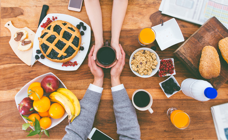 hand holding: couple having breakfast in the morning at home. Rich breakfast on the table and hot coffee