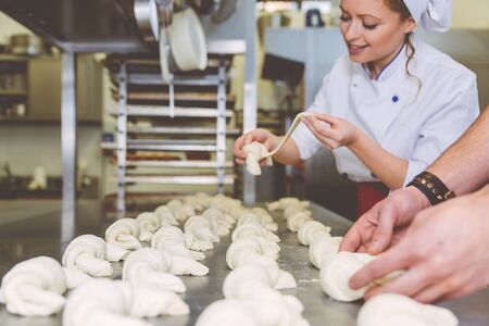 Chef preparing sweet croissant in the pastry shop laboratory. Industrial concept about food