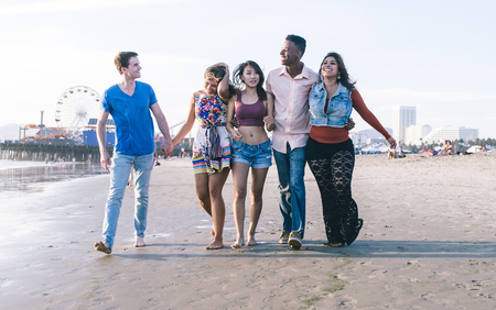 Mixed race group of friends walking in Santa monica beach Фото со стока