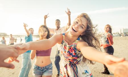 Grupo de amigos se divertindo e dançando na praia. festa de férias de primavera na praia Banco de Imagens