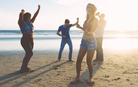 celebração: Grupo de amigos se divertindo e dançando na praia. festa de férias de primavera na praia Banco de Imagens