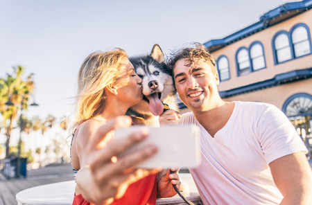 Happy couple taking a selfie with their husky - Woman holding cellphone and taking a funny picture with his family