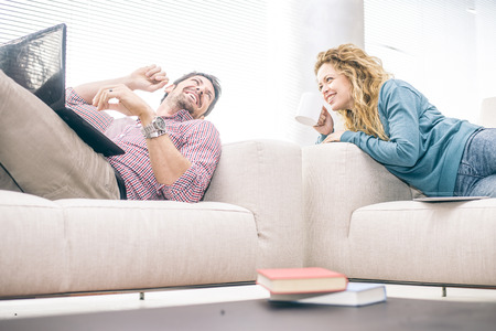 domestic life: Cheerful couple lying on the couch and looking at laptop computer - Partners talking and smiling while relaxing in the living room, domestic life scene Stock Photo