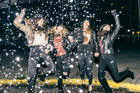 Pretty crazy girls dancing, throwing confetti and having fun - Young women partying outdoors before to go in a club