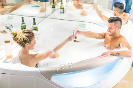 wife of bath: Couple of lovers toasting champagne glasses in a jacuzzi full of foam - Partners celebrating anniversary in a luxury spa resort