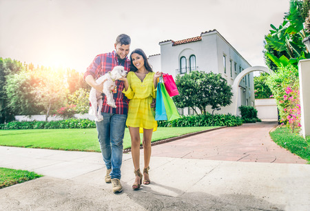 Couple with dog and real estate in the background - Rich people lifestyle - Cheerful couple in front of modern house