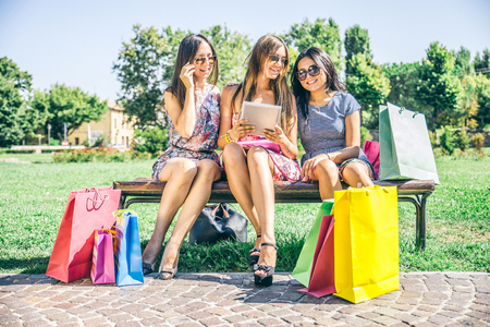 girl sitting: Three beautiful girls looking down at tablet - Women shopping online on a portable computer device - Best friends sitting outdoors and having pause from compulsive shopping