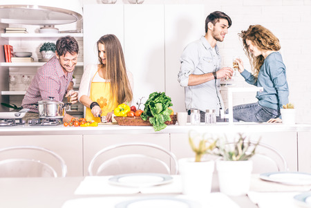 young adults: Group of friends at home party, woman cooking dinner for her guests - Young adults talking and having fun at home while preparing a delicious meal