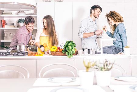pareja en casa: Grupo de amigos en el partido en casa, mujer cocinar la cena para sus invitados - Los adultos jóvenes de hablar y divertirse en casa mientras se prepara una deliciosa comida