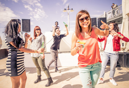 Portrait of happy friends dancing at party - Cool people drinking alchool and having fun in a bar while dj is mixing music Stock Photo