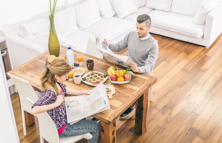 forniture: Couple reading newspaper while having breakfast in the morning - Domestic life, family living in a modern house