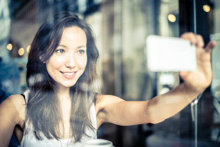 taking photograph: Beautiful woman taking a selfie in a bar, view from outside the window shop - Pretty mixed race girl photographing herself for sharing on social network Stock Photo