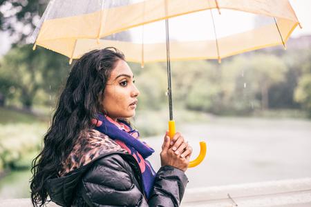 sotto la pioggia: Donna che cammina in un parco con ombrello mentre piove - Pretty ragazza in attesa di qualcuno sotto la pioggia