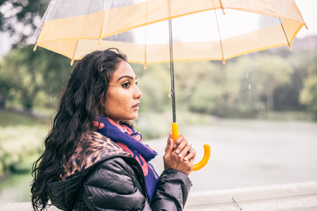sunny cold days: Woman walking in a park with umbrella while raining - Pretty girl waiting somebody under the rain Stock Photo