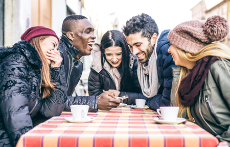 group meeting: Multi-ethnic group of friends sitting in a bar and drinking coffee and watching a funny video on a cellular phone - Cheerful students meeting in a coffee house for a break