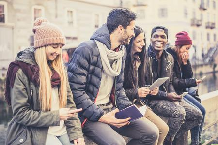 personas sentadas: grupo multicultural de amigos utilizando tel�fonos celulares - Los estudiantes que se sientan en una fila y escribir en los tel�fonos inteligentes Foto de archivo