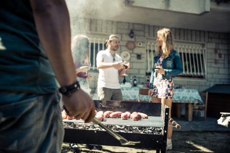 Amis dans la maison jardin griller la viande et avoir du plaisir - Groupe de personnes au barbecue de boire du vin de fête Banque d'images
