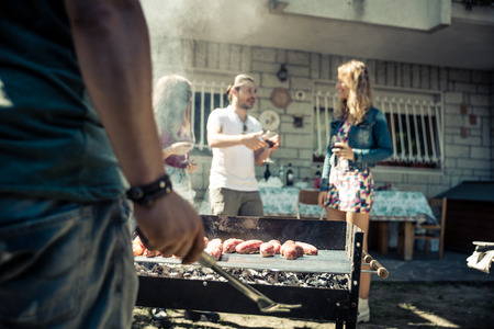 Friends in home garden grilling meat and having fun - Group of people at barbecue party drinking wine Stock Photo