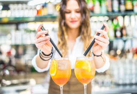 cocteles: Barmaid preparación de cócteles en un bar para sus clientes - Camarero en el trabajo en un club