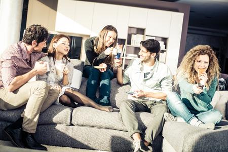 Grupa przyjaciół mówienia i zabawy siedząc na kanapie - Wesoła ludzie spotykają się w domu przyjaciela na kawę