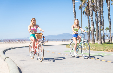 Two women riding on bikes - Pretty girlfriends relaxing on a summertime vacation Stock Photo