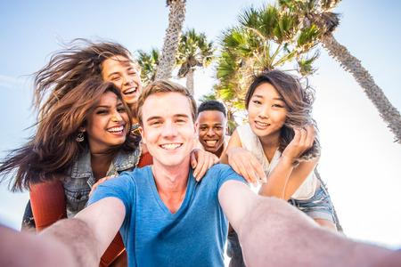 携帯電話カメラでセルフ ポートレート写真を撮る友人の多民族のグループ - 多様な民族と楽しい夏休みのアウトドア パーティーの陽気な人々
