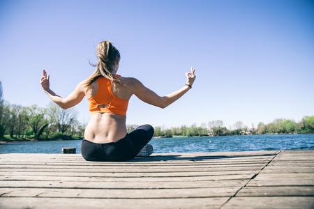 body scape: Woman practicing yoga in front of a lake - Girl relaxing and meditating after a workout session