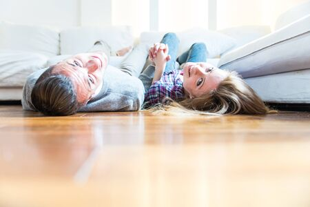 Couple of lovers in the living room holding hands and lying on sofa,concepts about domestic life, relationship and living togeyher Stock Photo