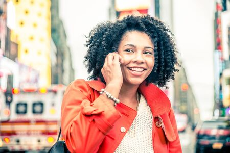 sidewalk talk: Afroamerican woman speaking at phone, urban blurred background - Portrait of pretty girl talking at somebody on cellphone and smiling Stock Photo