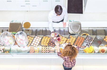 Camarero que sirve al cliente en una pastelería, vista desde arriba - compra de la mujer pasteles y galletas para el desayuno