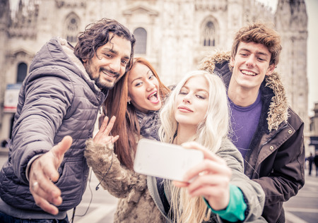 Group of friends of diverse ethnics taking a picture while grimacing - Cheerful young people photographing themselves while sightseeing a city Stock Photo