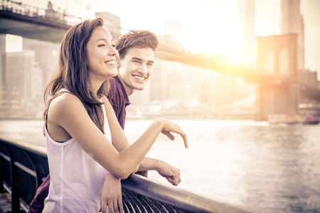 romantic date: Cheerful couple talking and having fun on a romantic date - Two friends having fun while looking sunset over Manhattan Stock Photo