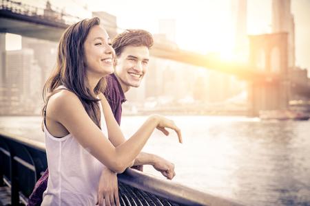 Coppia allegra parlare e divertirsi su un appuntamento romantico - Due amici che hanno divertimento mentre guardando tramonto su Manhattan Archivio Fotografico - 52900033