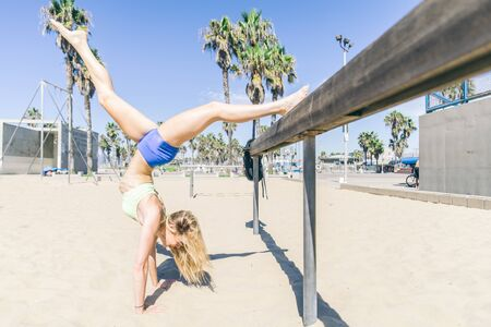 girl working out: Woman doing stretching exercise on the beach - Sportive girl working out Stock Photo