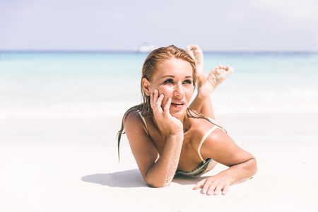 view woman: Beautiful woman lying down on a tropical beach with white sand Stock Photo