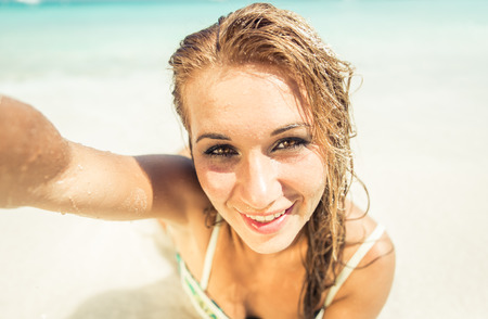 woman lying down: Woman lying down on white sand and taking selfie Stock Photo