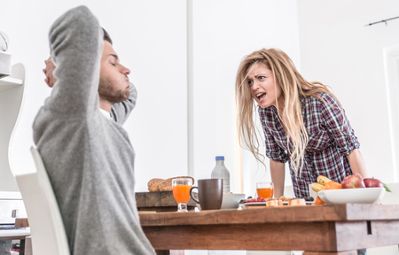 and the horizontal man: Couple fighting in the morning. woman screaming to her man. relationship problems Stock Photo