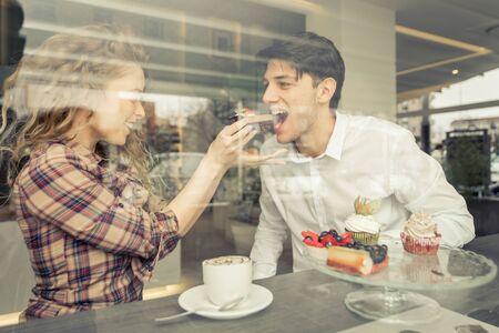 Jong paar eten gebakjes in een patisserie Stockfoto