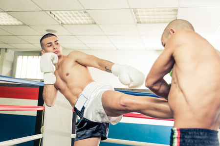 two men: Kickboxers training on the ring. Kicking and blocking the hit