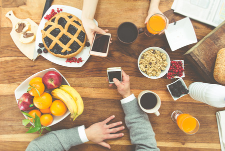 food and wine: couple having breakfast in the morning at home,smartphones in their hand. Rich breakfast on the table and hot coffee. Stock Photo