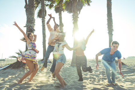 san: Group of friends making party on the beach and dancing together