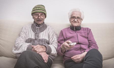 Vieux couple et zapping. couple de personnes âgées à regarder la télévision sur le canapé