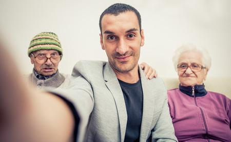 祖父母と家族の肖像画。スマート フォンと selfie 写真素材