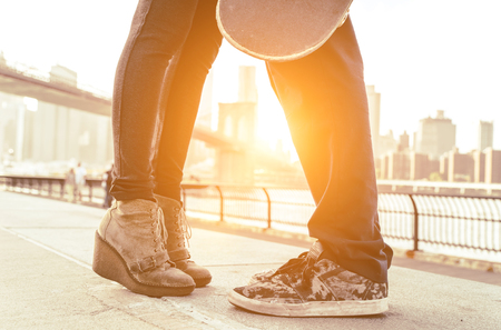 skateboard shoes: Kiss in Brooklyn. Teenager couple kissing in New york. Brooklyn bridge in the background
